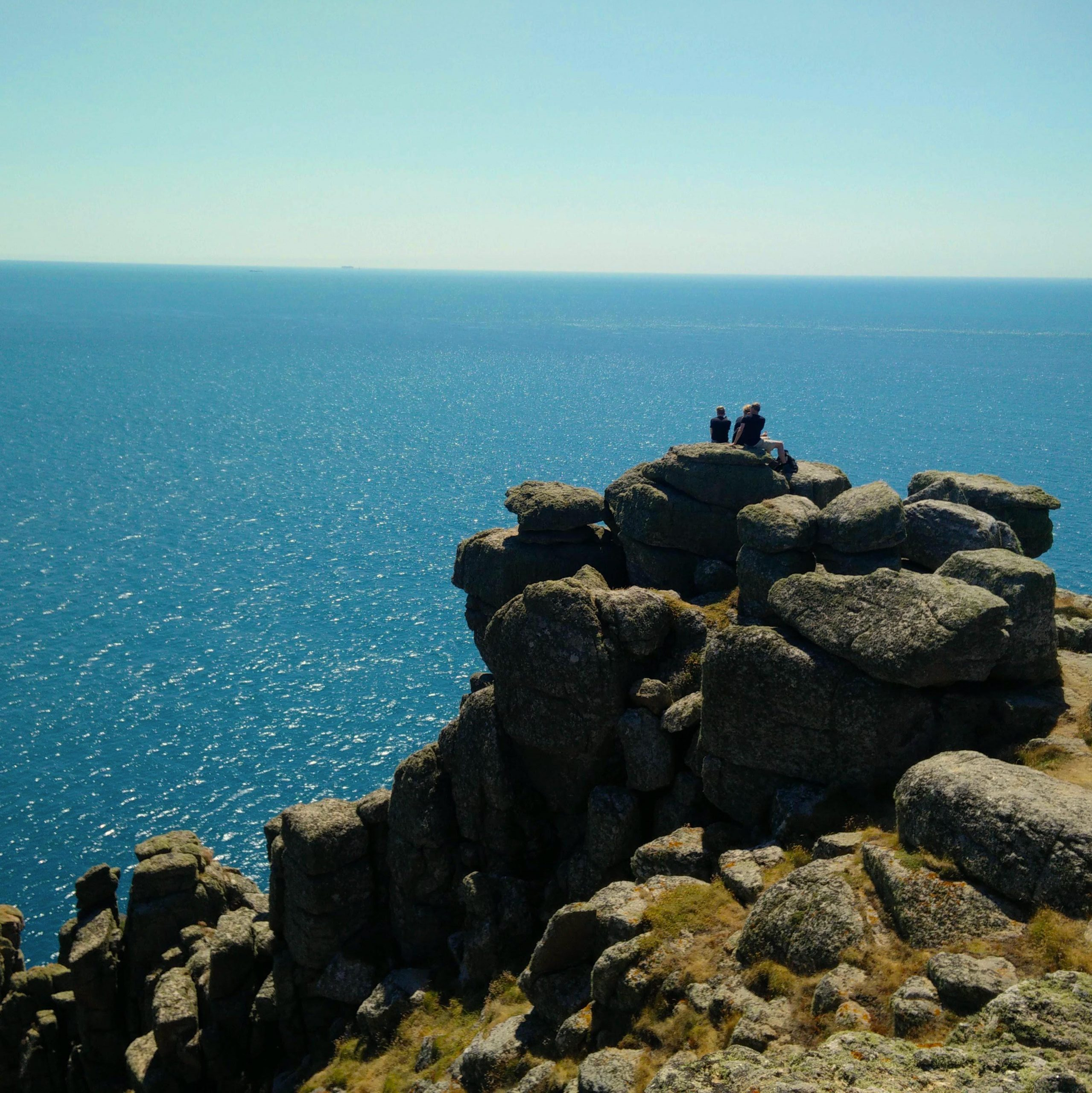 A small group overlooking the ocean from the edge of a cliff at Cornwall.