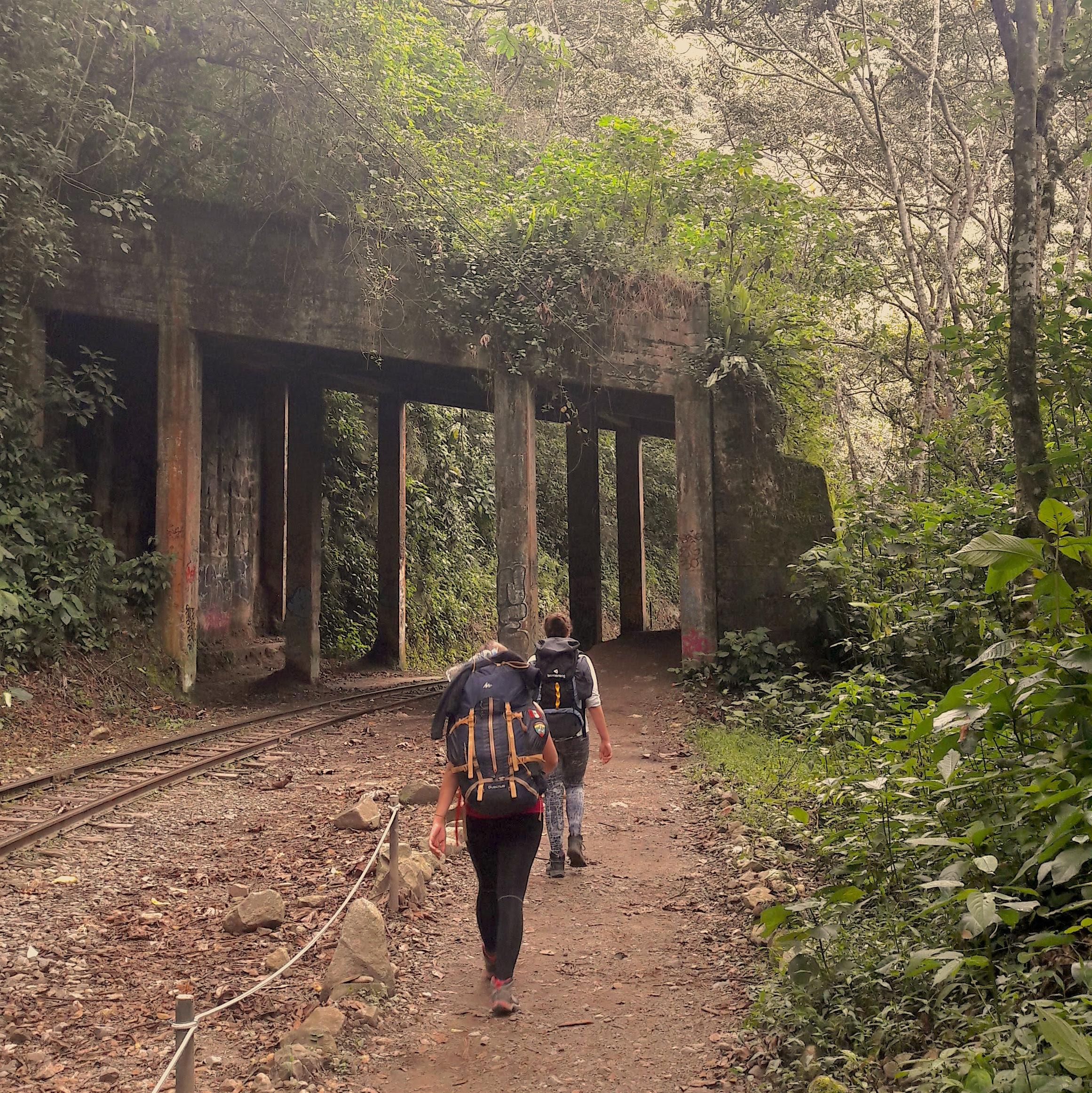 Two women with backpacking backpacks walking alongside train tracks towards a tunnel.