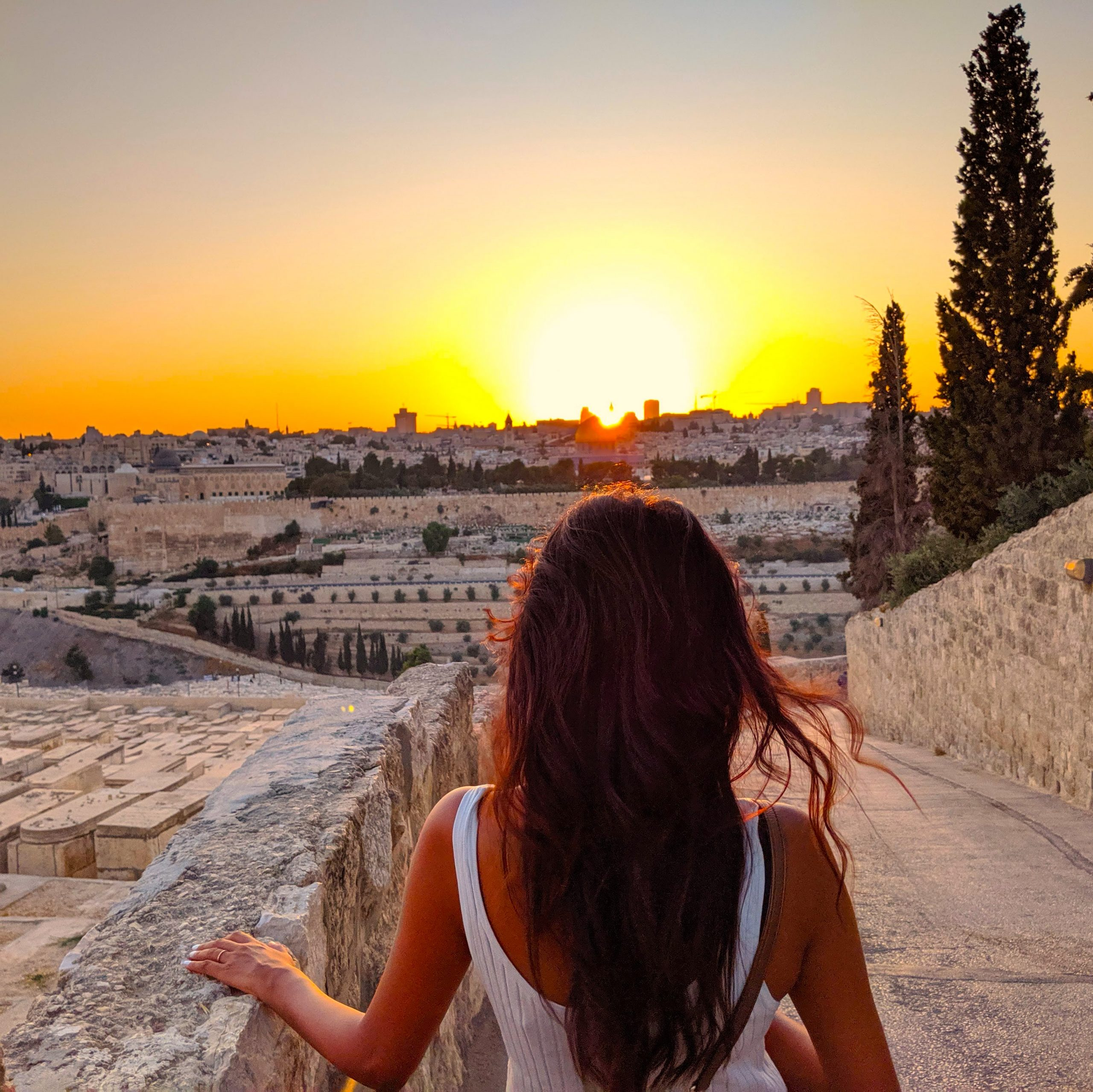 Woman looking at the sun set over an old city