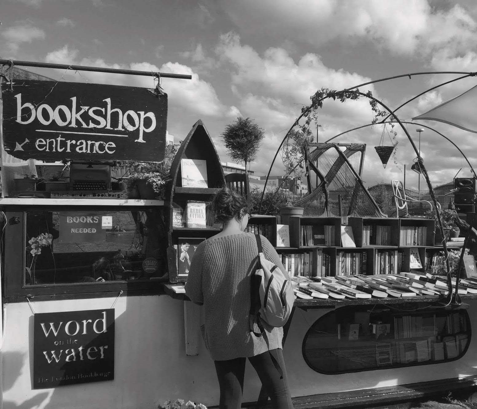 A woman looking at books on a canal boat bookshop