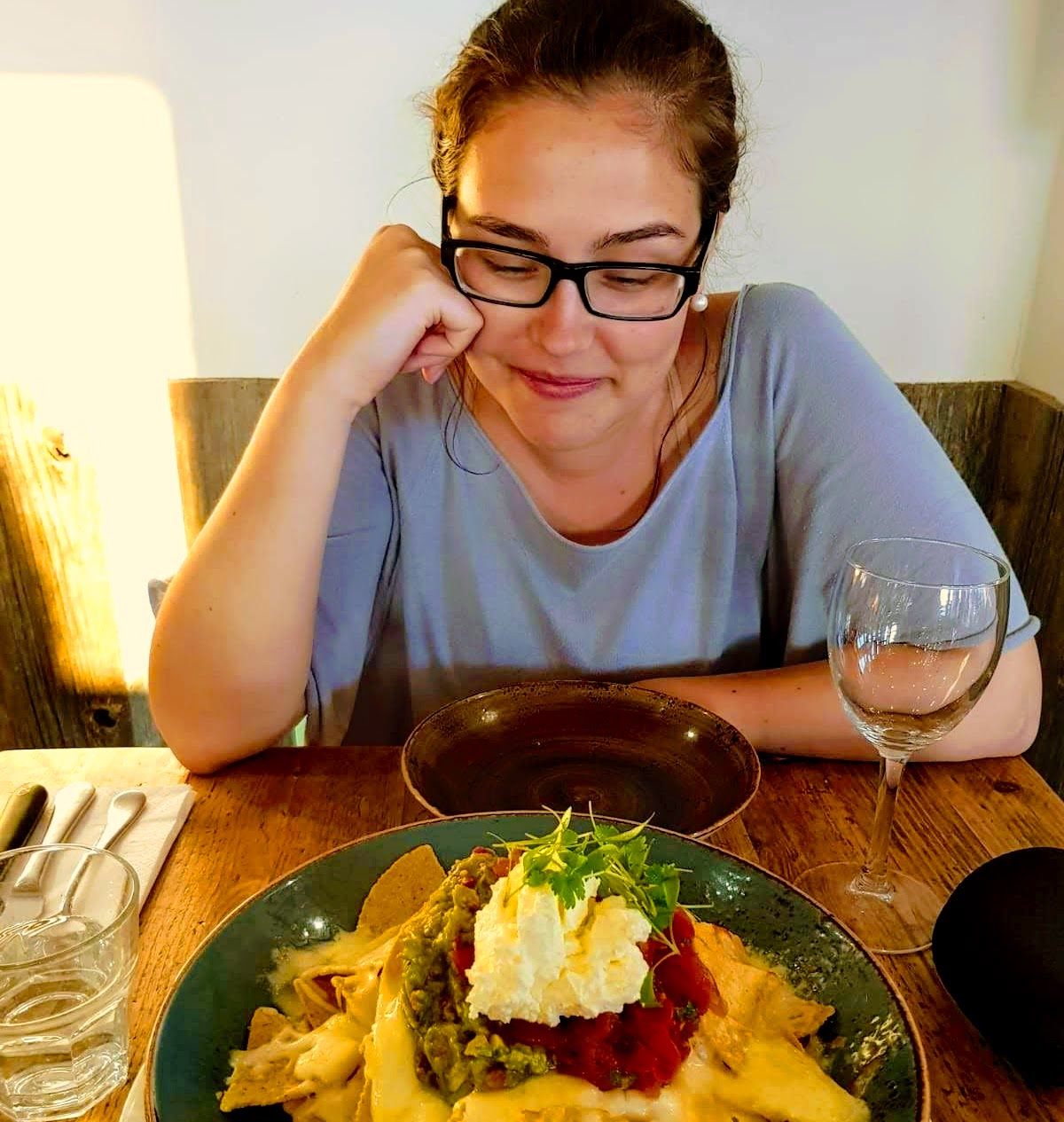 Woman looking longingly at a plate of nachos